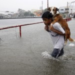 A boy carries his dog whilst wading in floodwaters brought by the monsoon rain, intensified by tropical storm Trami, in Paranaque city